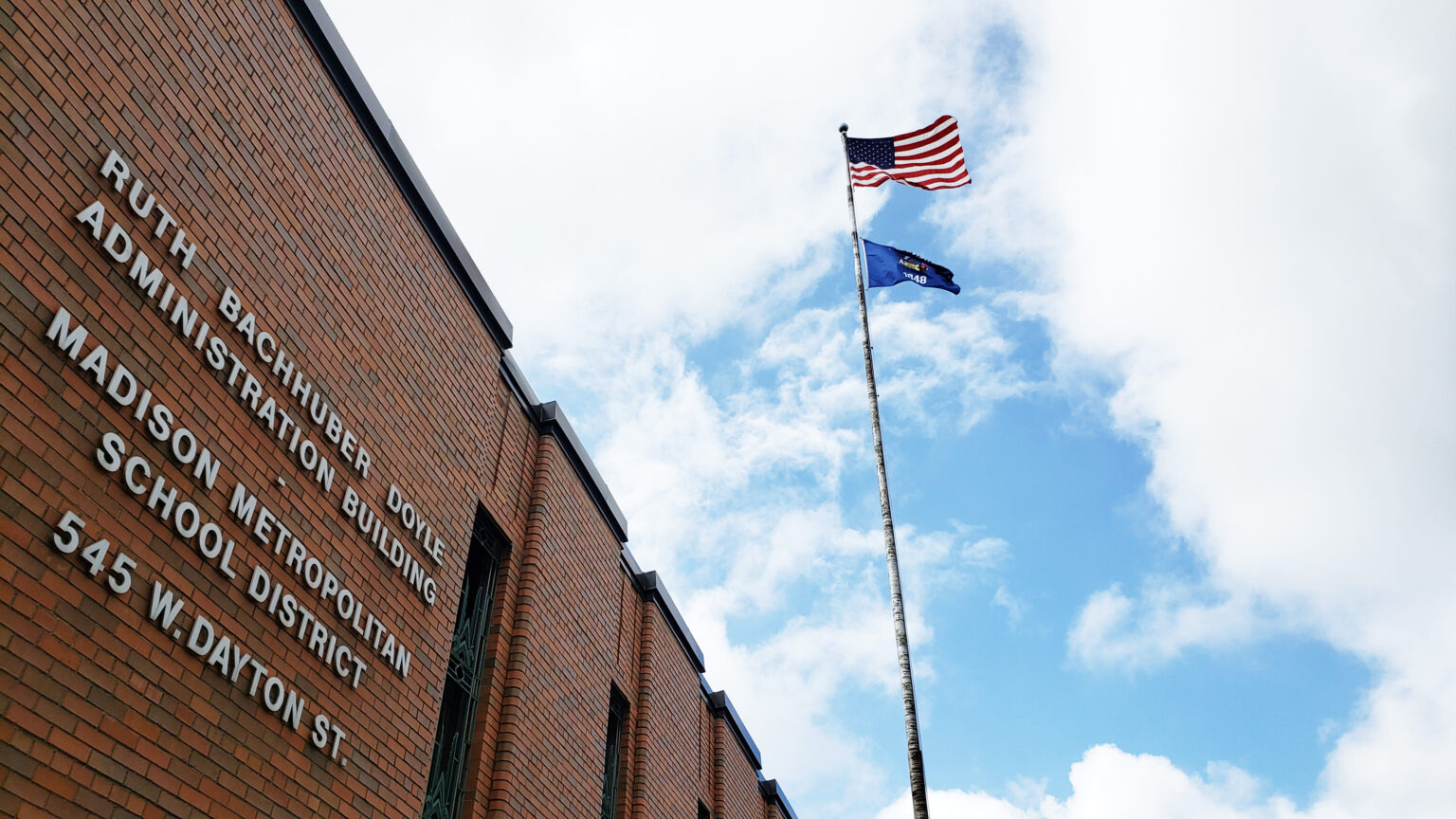 A view of the Madison Metropolitan School District administrative office building with a flag pole flying the USA and Wisconsin flags