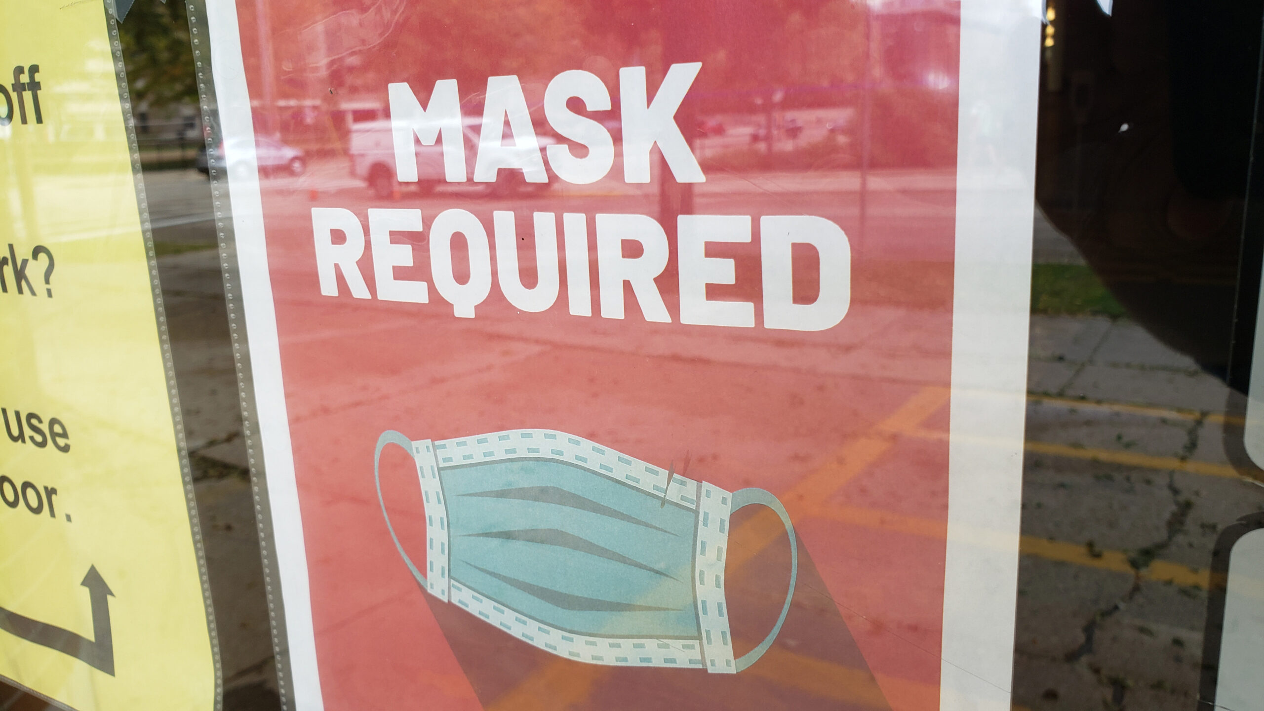 """A sign with an illustrated surgical mask reads """"MASK REQUIRED."""""""