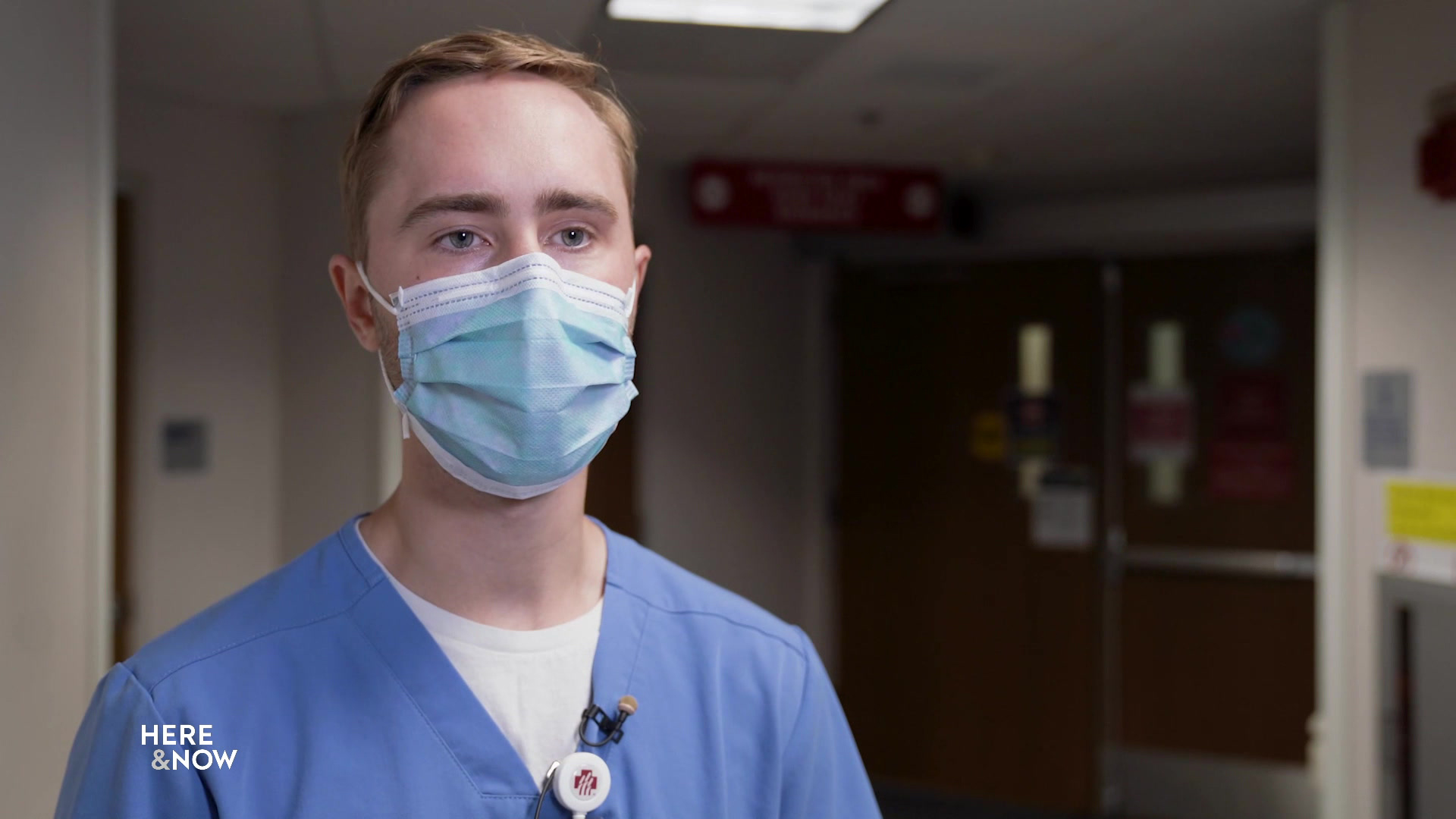 Ryan Letsch wears a mask while standing in a hospital hallway.