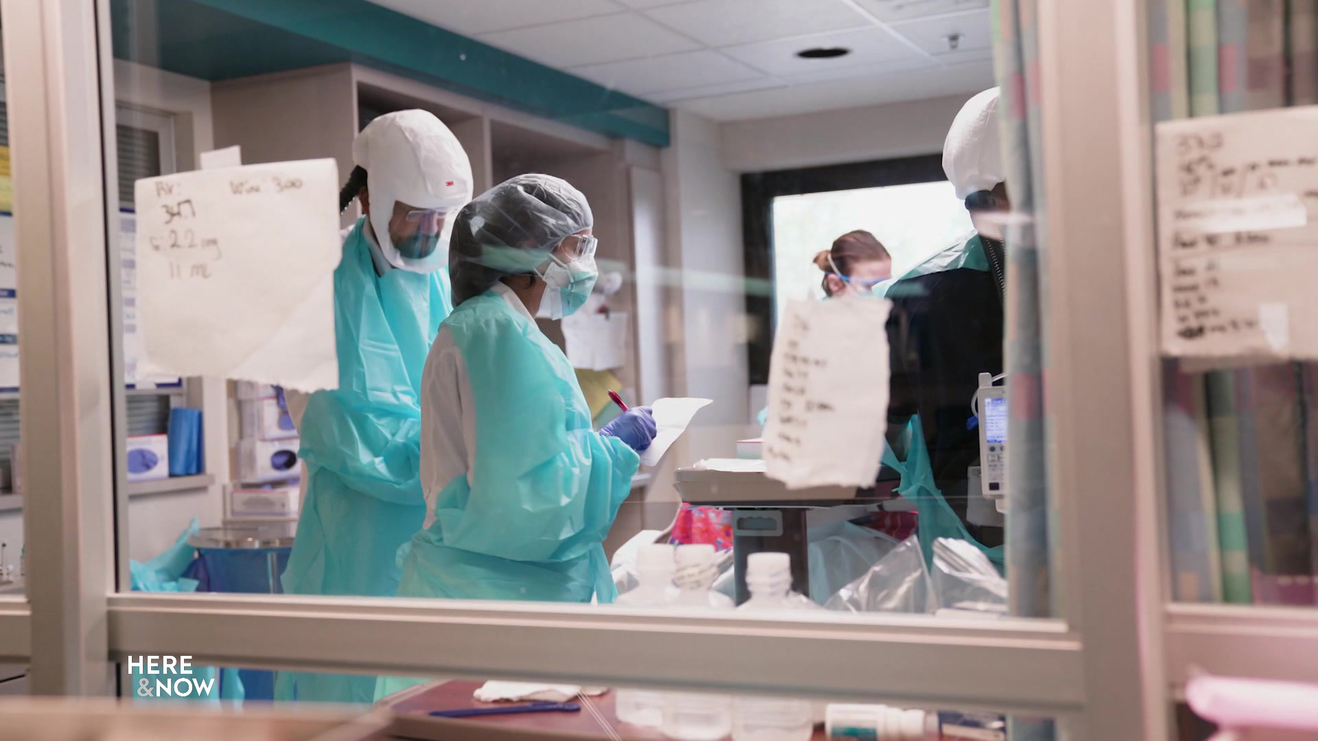 Hospital staff wearing personal protective equipment in an ICU room.