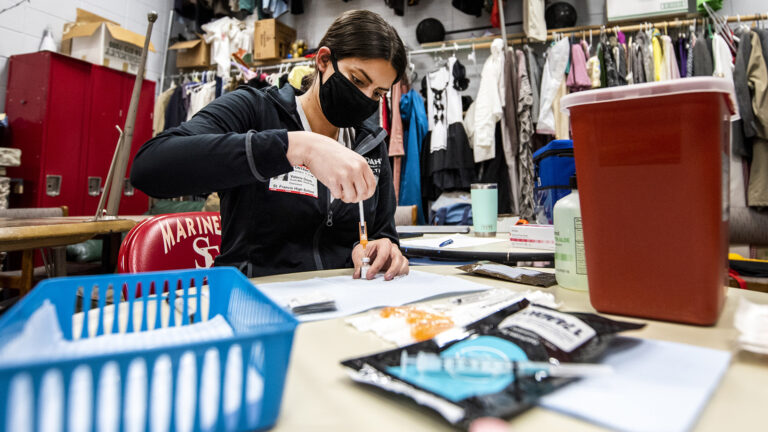 A nurse prepares a syringe in a storage room with theater costumes hanging in the background.