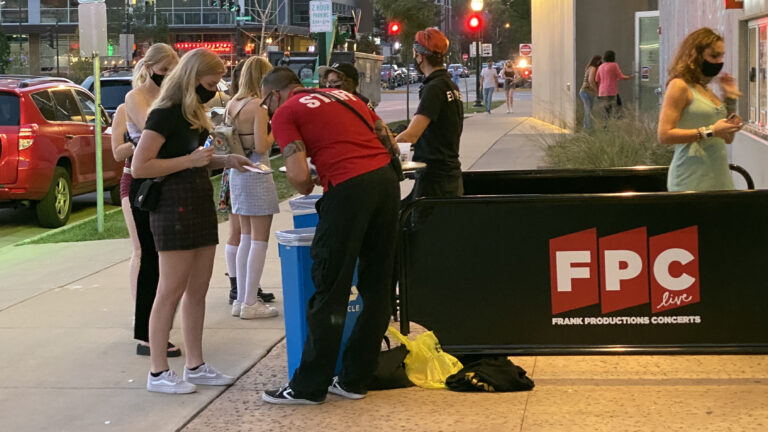 Staff members check IDs and proof of vaccine cards of concert-goers outside a venue in downtown Madison, Wisconsin.