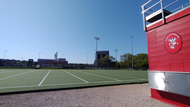 A red conductor's podium overlooks the green turf of the UW Marching Band's practice field on the UW-Madison campus.