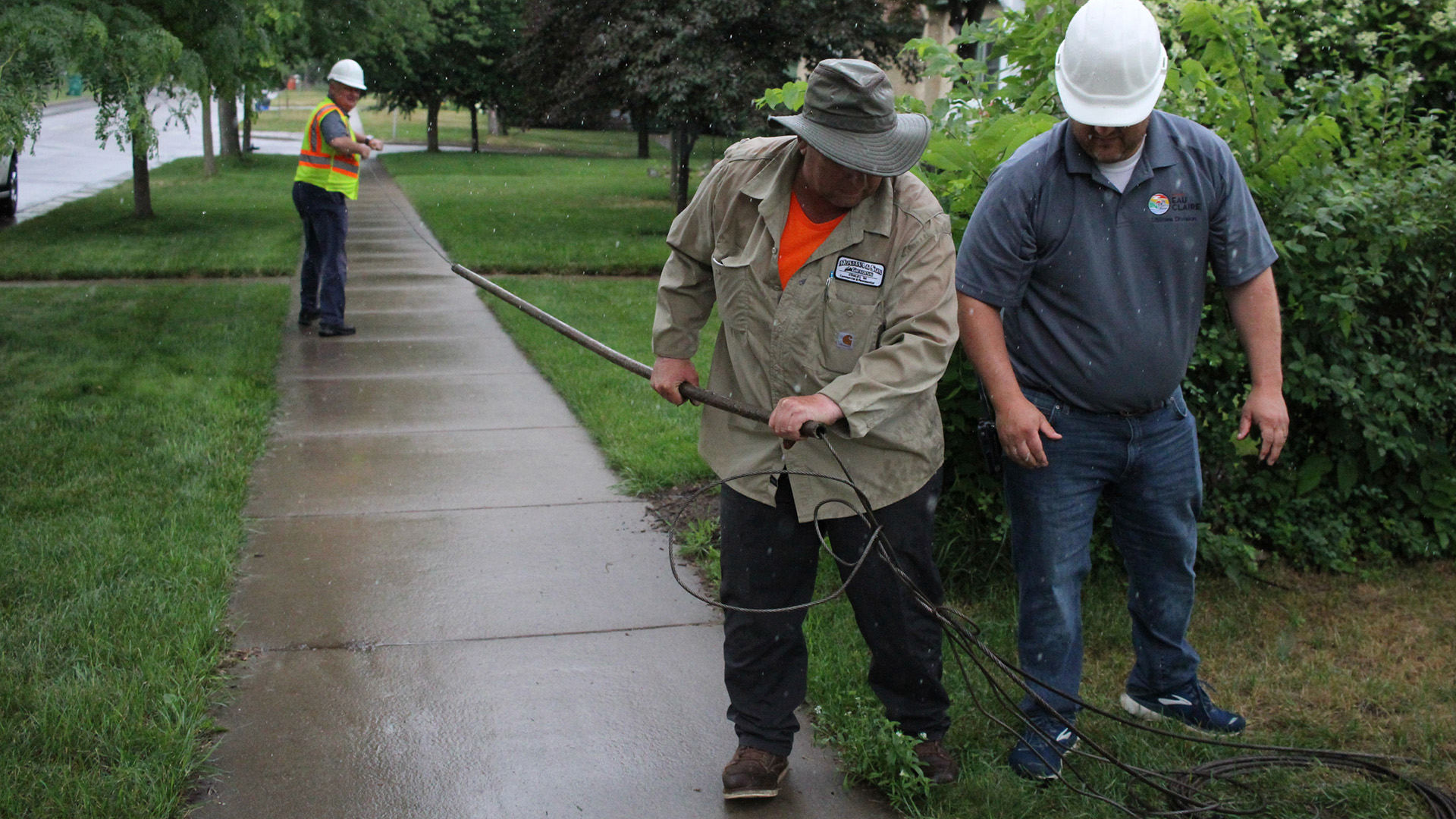 Workers stand on a sidewalk and lawn holding a lead pipe and cords.