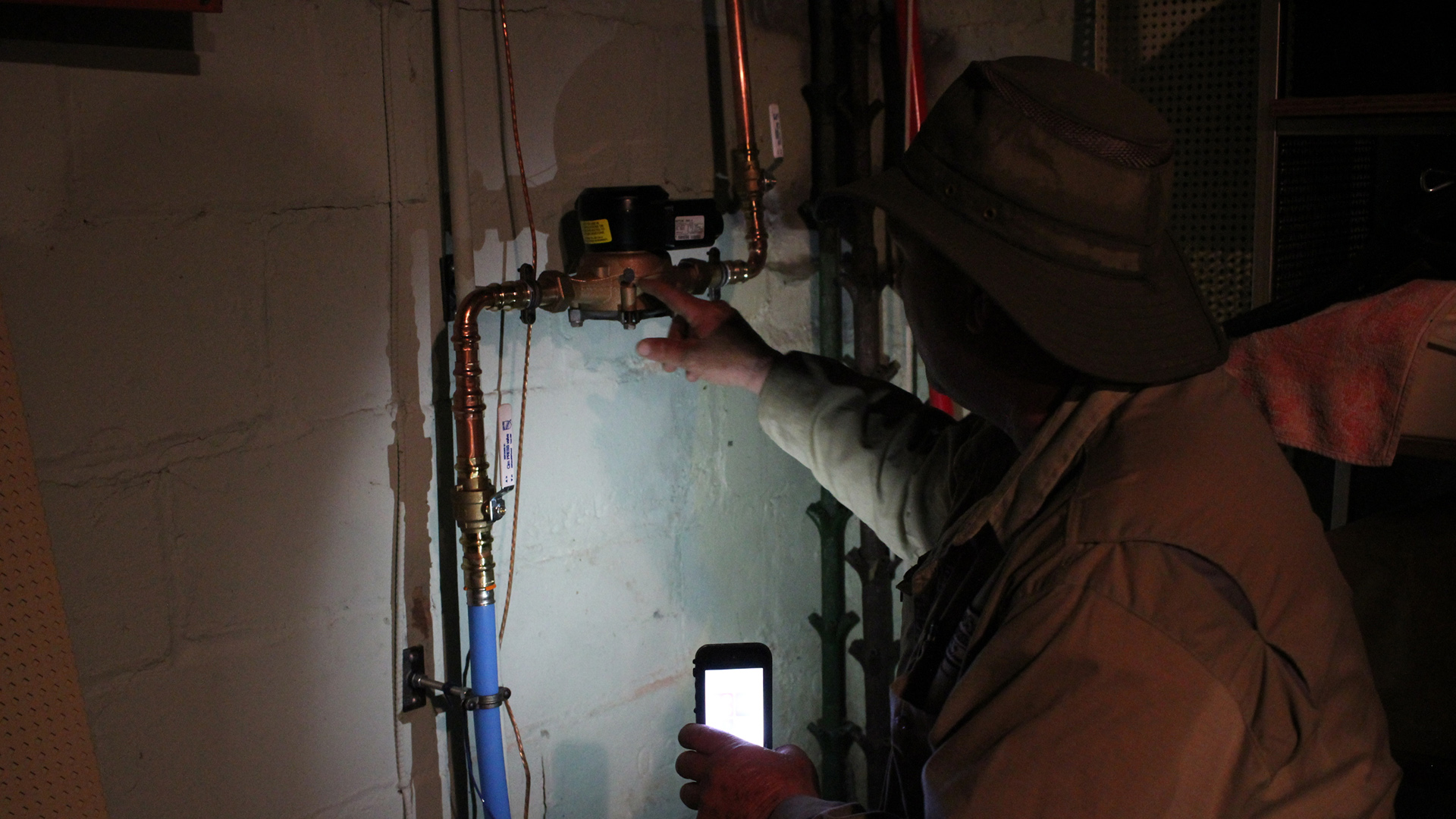 A worker examines a pipe connection in the dark basement of a house holding a smart phone for illumination.