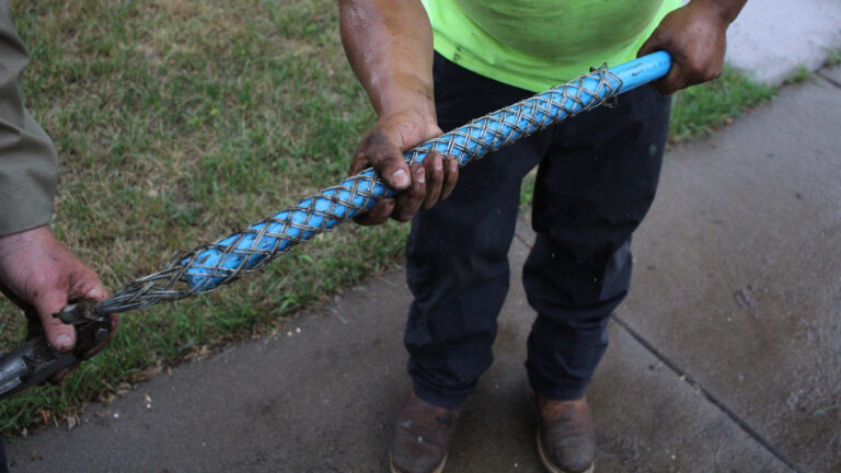 Workers hold a blue replacement water pipe surrounded by metal netting.