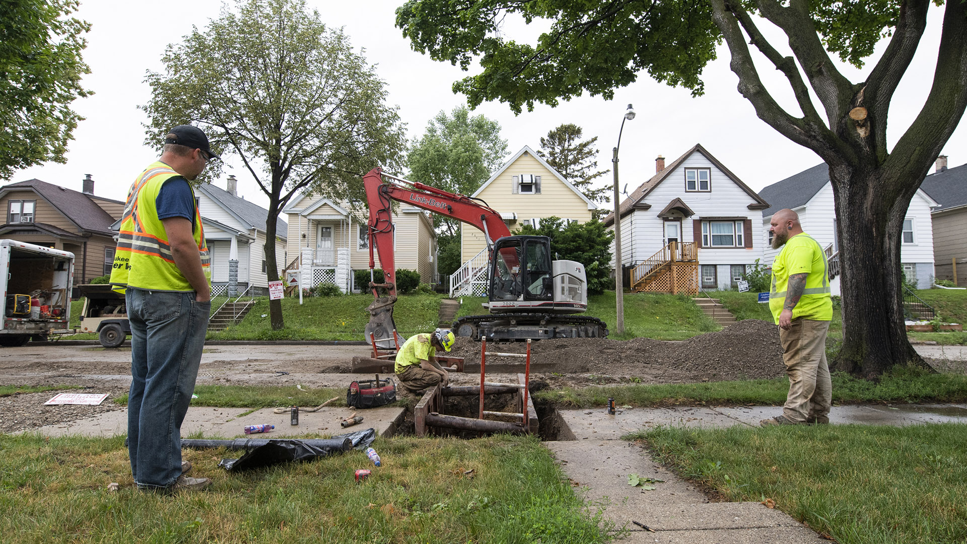 Workers stand on a lawn and sidewalk next to an excavated pit with a backhoe in the background.