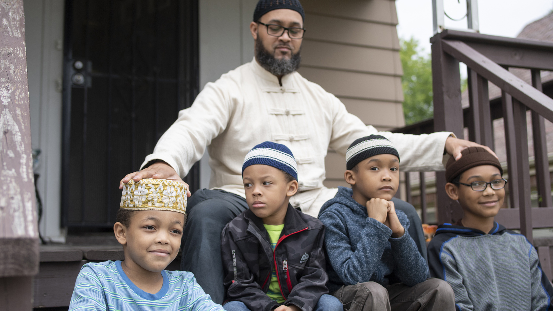 Nazir Al-Mujaahid sits on the front steps of a house with four children.