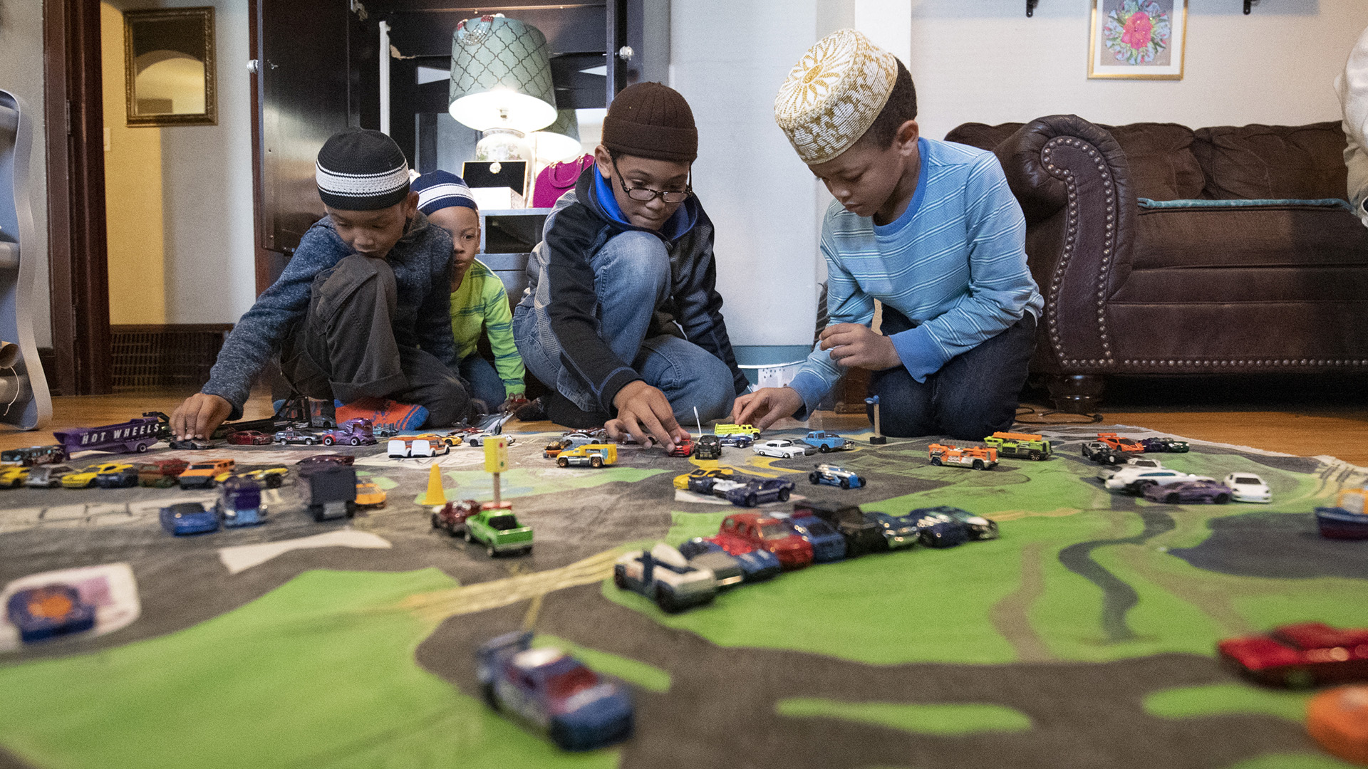 Children play with toy cars on the floor.