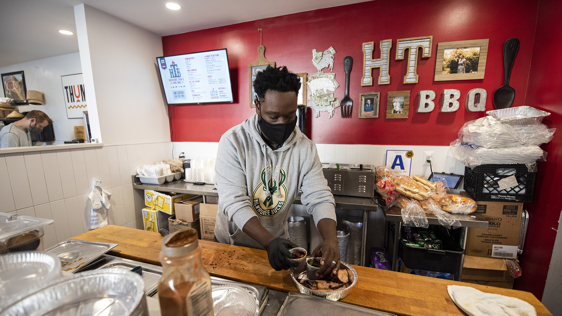 Jason Alston prepares a to-go food container behind a counter.