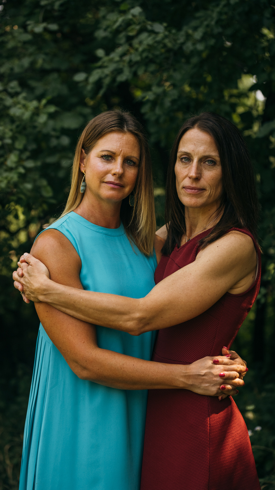 Jennifer Moston and Tracy hug while standing in front of foliage.