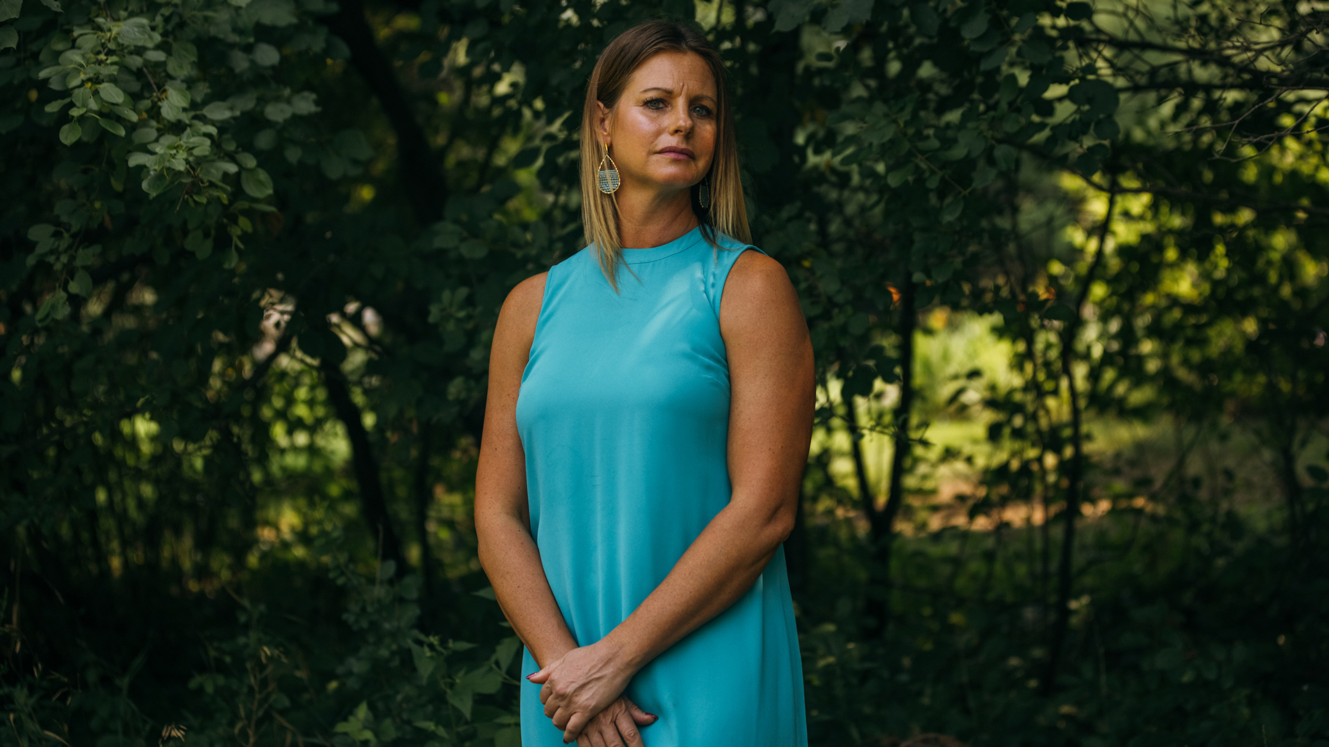 Jennifer Moston stands in front of foliage.