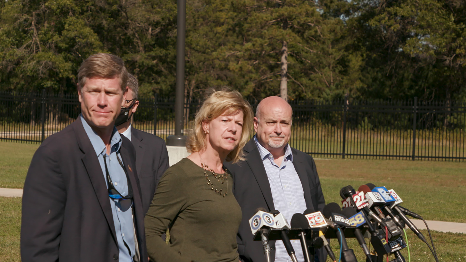 Ron Kind, Tammy Baldwin and Mark Pocan stand in front of microphones at a podium in front of a wrought-iron fence.