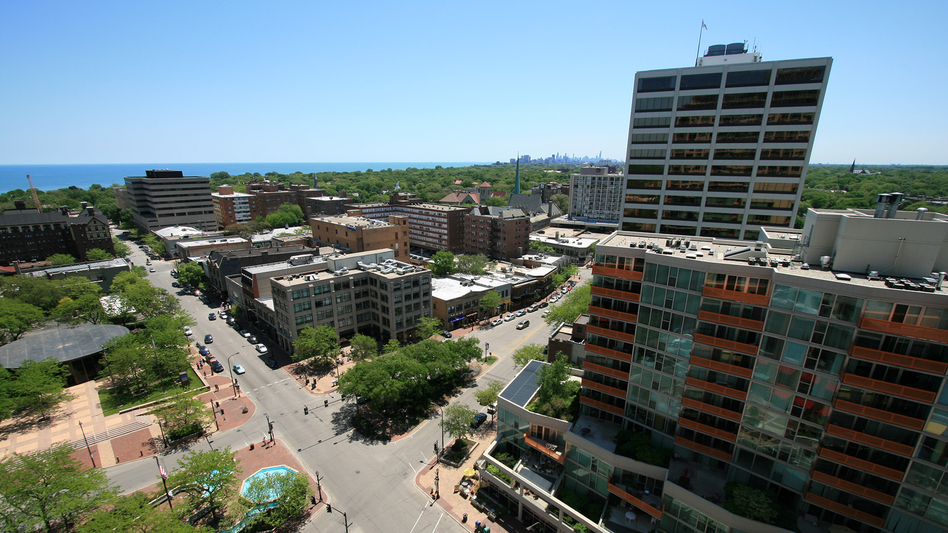 A high view of buildings around Fountain Square in downtown Evanston, Illinois, with the skyline of Chicago in the distance.