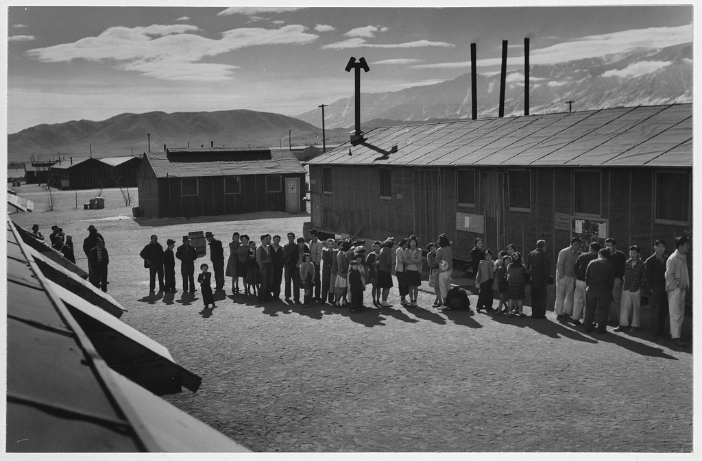 A black-and-white photo shows Japanese Americans stand in a line outside a building at the Manzanar interntment camp in 1943.