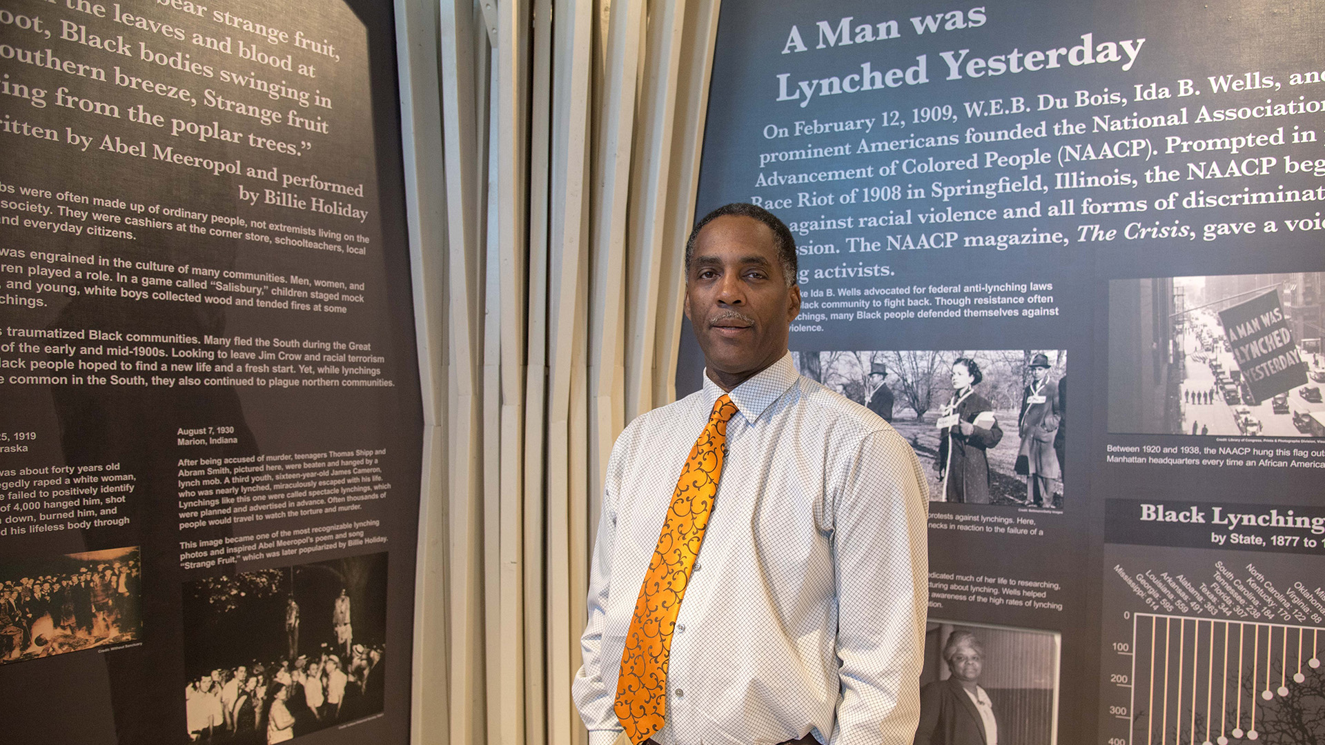 Reggie Jackson stands in front of historical displays at America's Black Holocaust Museum