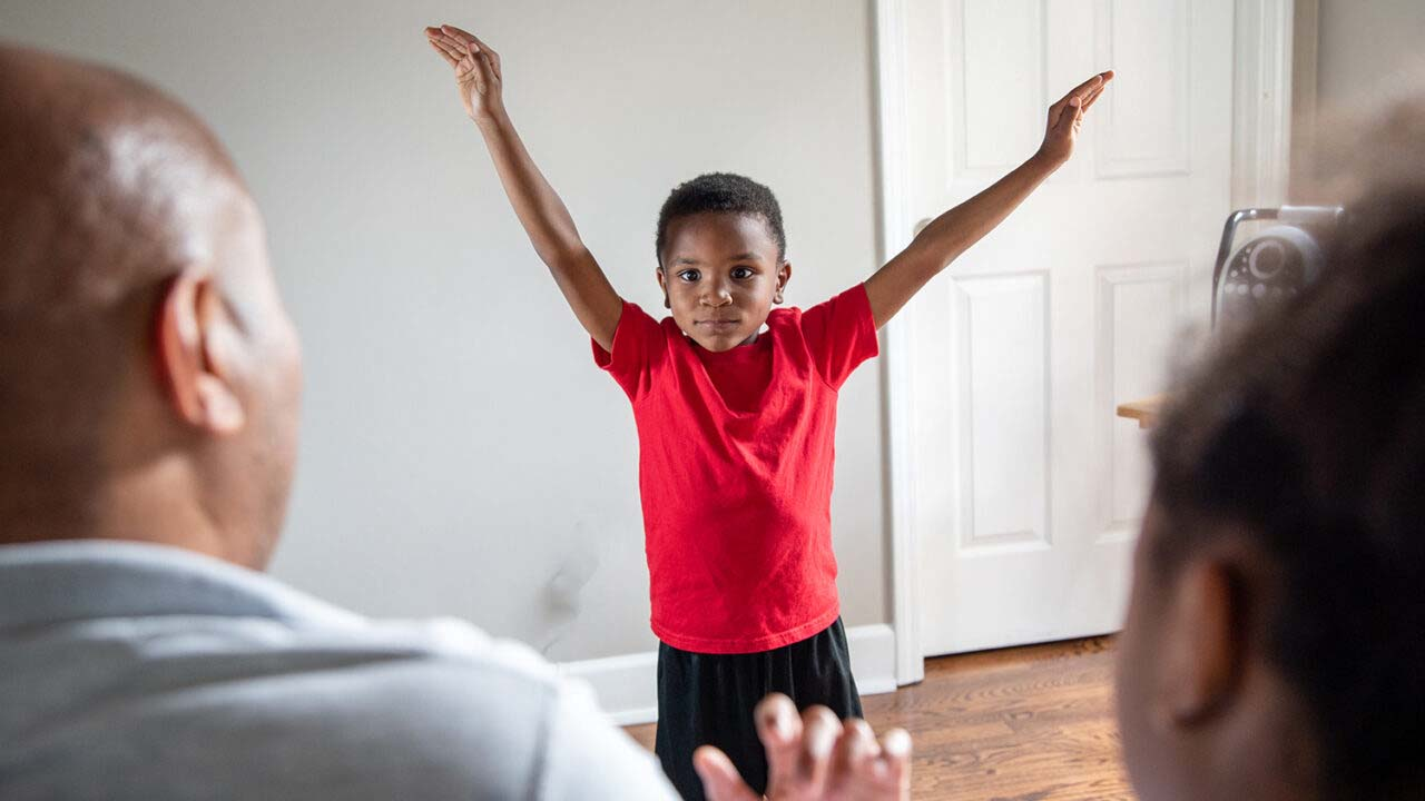 A little boy in a red t-shirt stands in front of his caregivers holding his arms up like he is flying