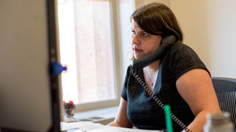 Claire Woodall-Vogg sits at a desk with an office phone resting betweeen her ear and shoulder.
