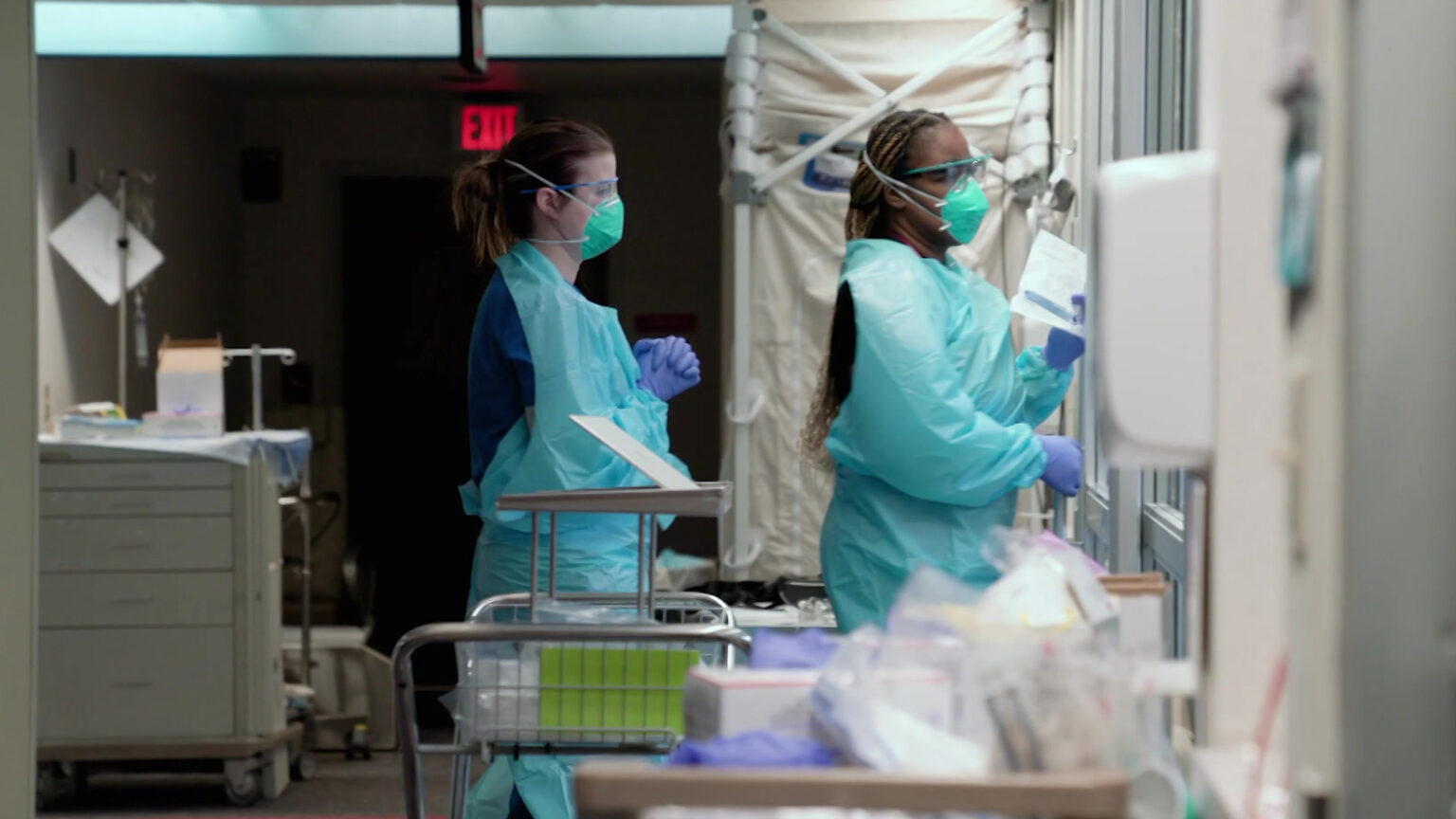 Two people wear medical gowns, gloves, masks and goggles as they prepare to enter a room inside a hallway filled with medical equipment