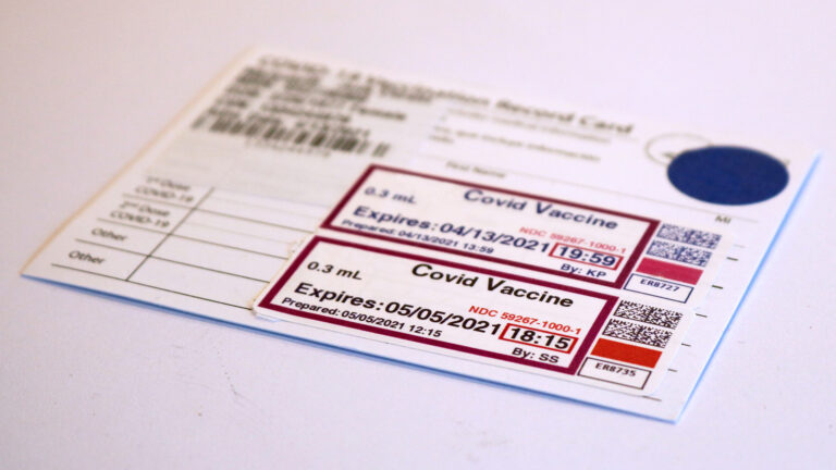 A COVID-19 vaccination record card with stickers noting two doses sits on a white surface.