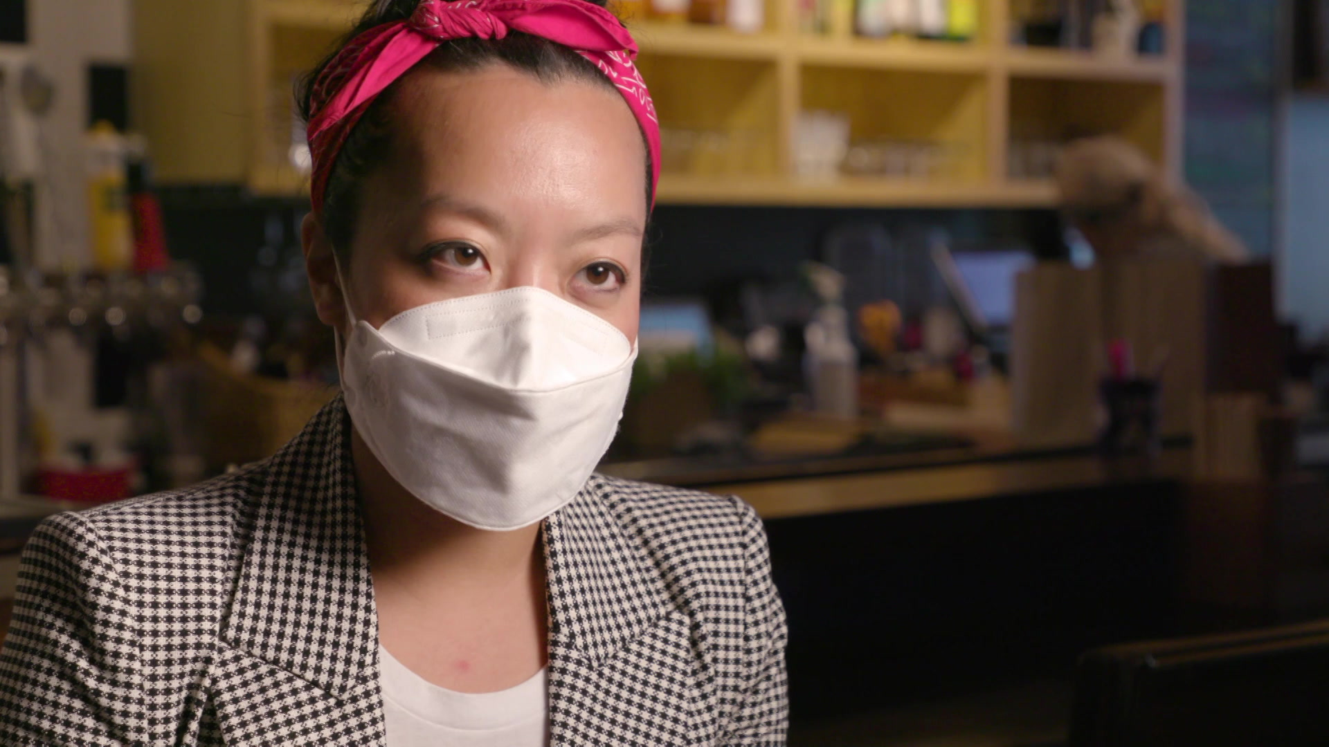 A portrait of Francesca Hong, wearing a suit and face mask with beer taps and cabinets in the background.