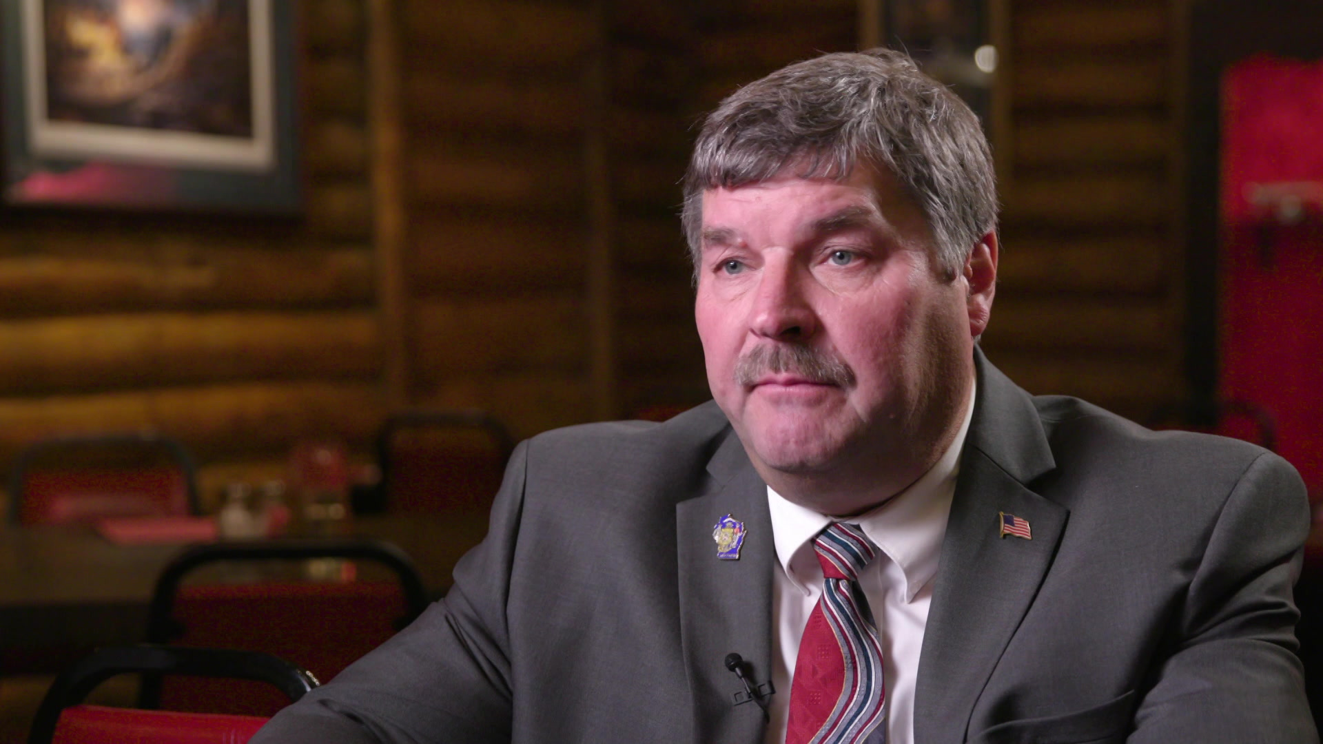 A portrait of Al Swearingen, wearing a suit with tables and a log-cabin style wall in the background.