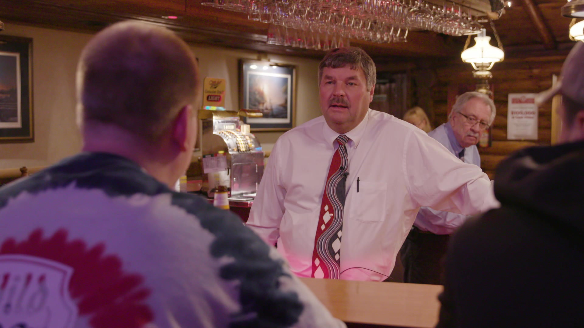 Rob Swearingen stands behind a bar and speaks to seated customers.