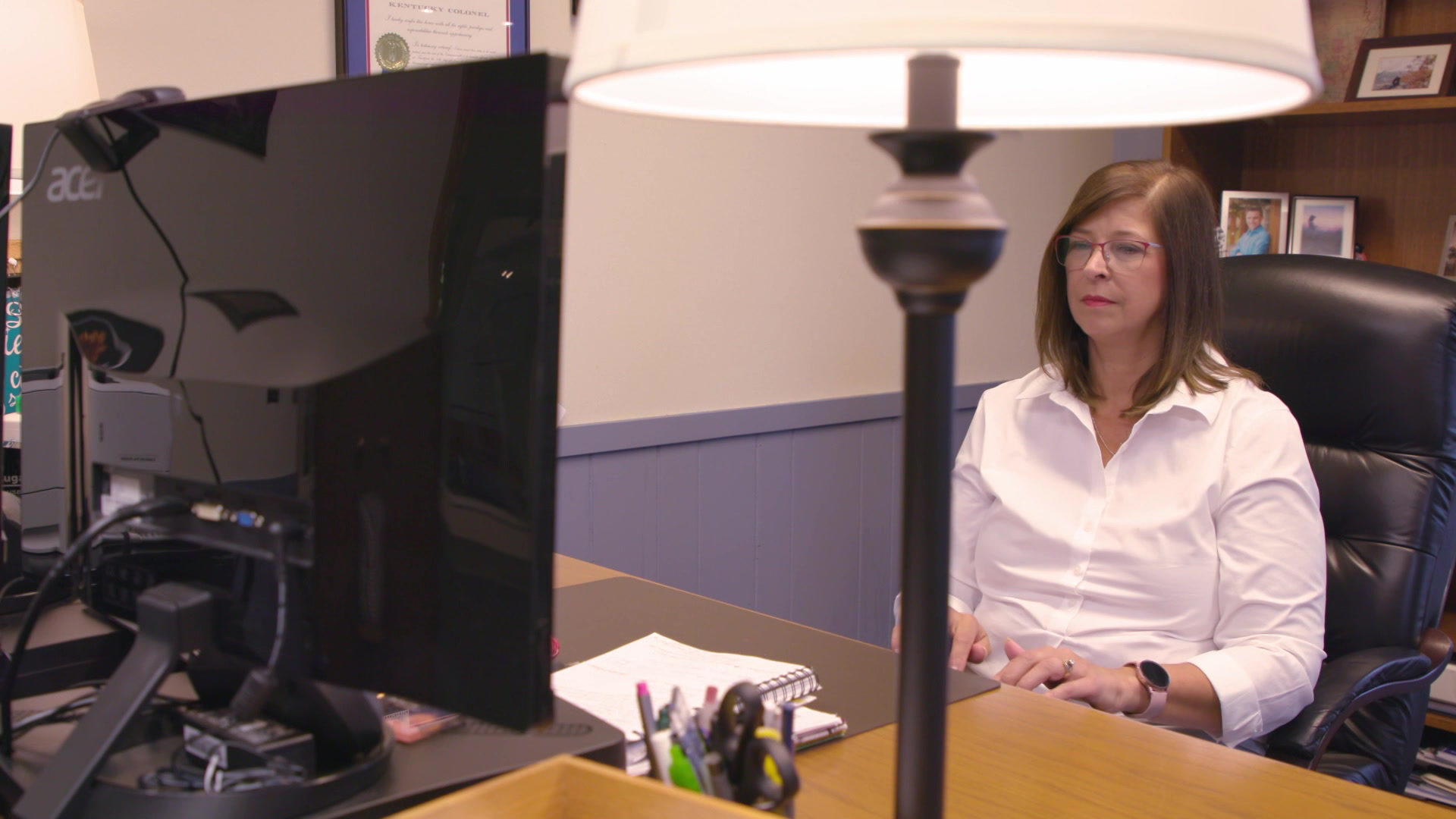 Kristine Hillmer sits at a desk and types on a keyboard with a lamp and computer monitor in the foreground.