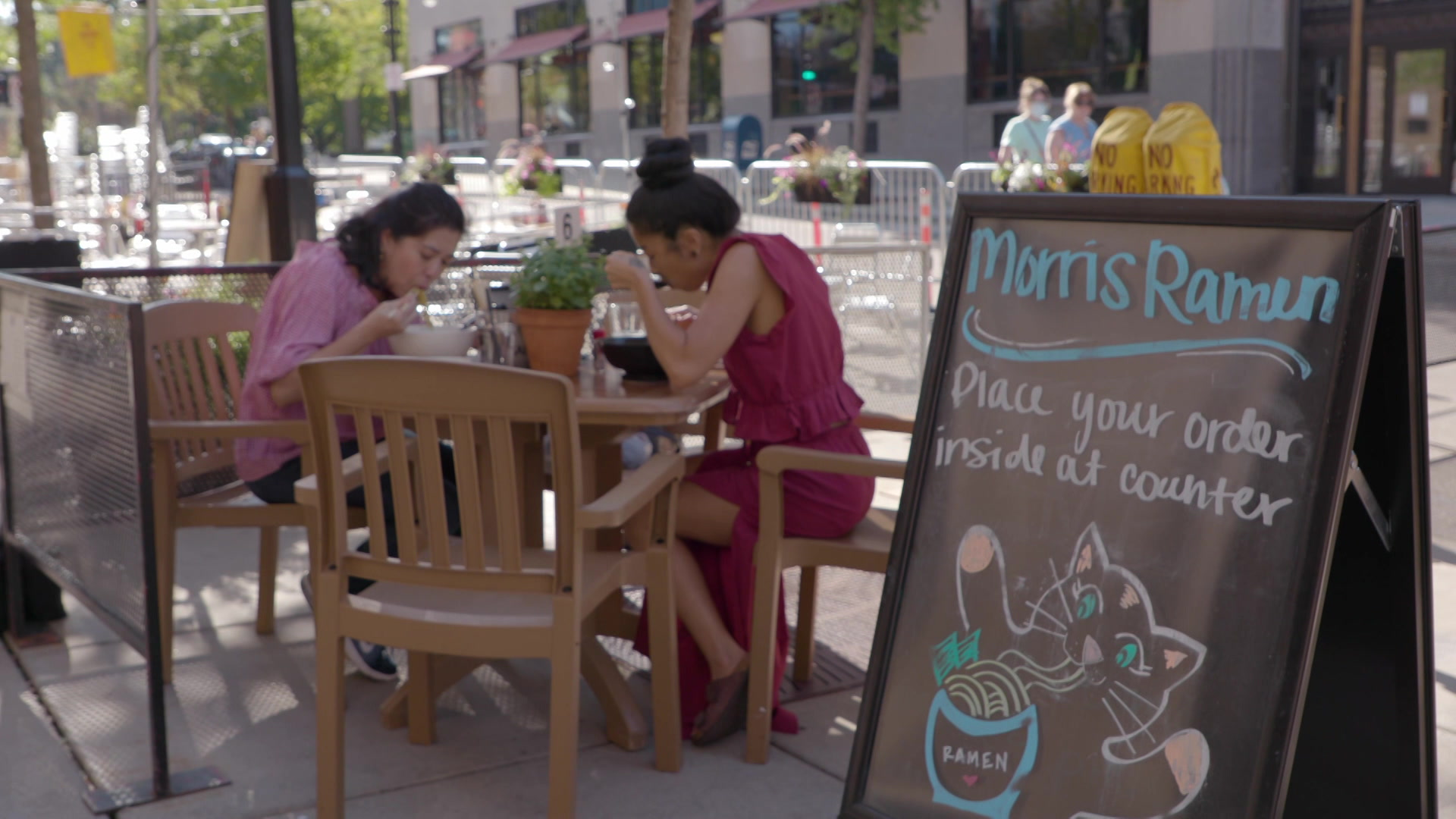 """A sidewalk sign with an illustration of a cat slurping noodles reads """"Morris Ramen: Place your order inside at counter"""" with dinners seated at a sidewalk table in the background."""