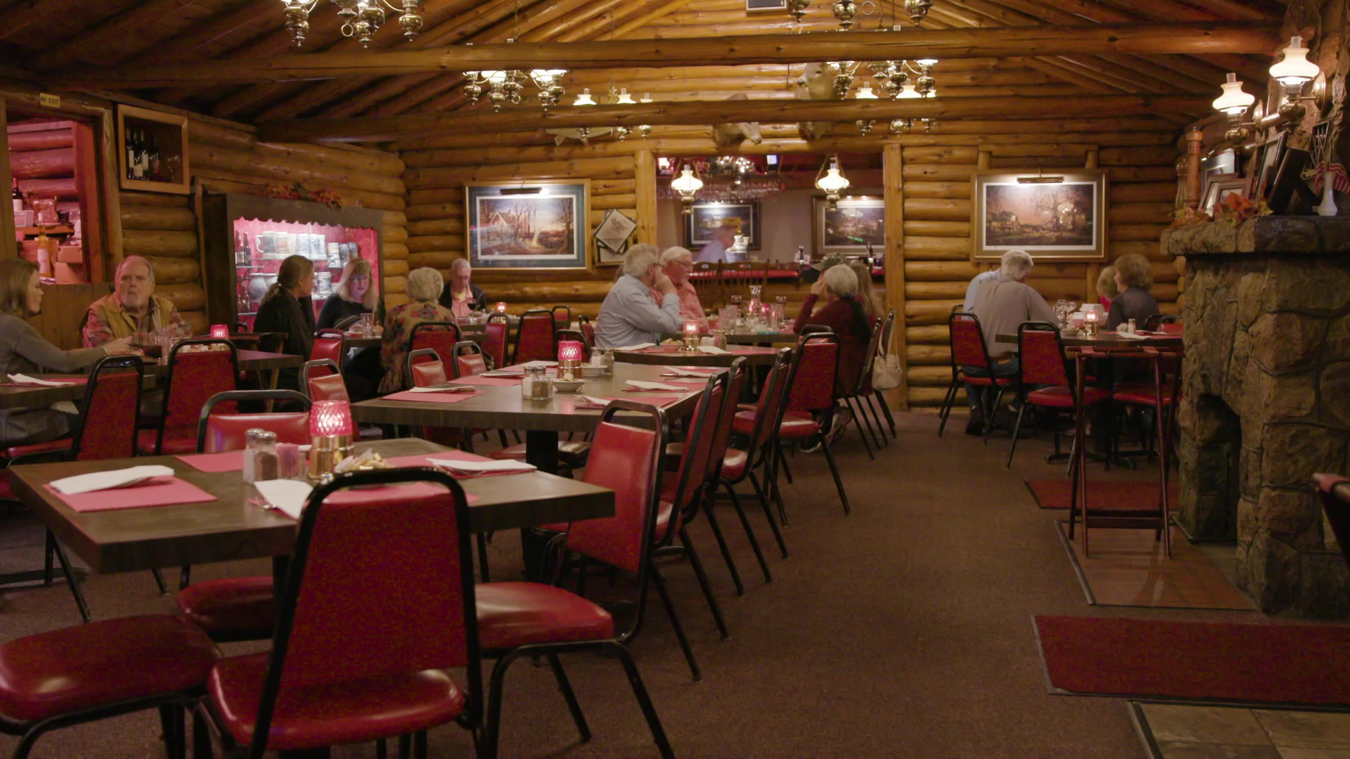 Dinners sit on red chairs and at tables inside a dining room with log walls and a stone fireplace at right.