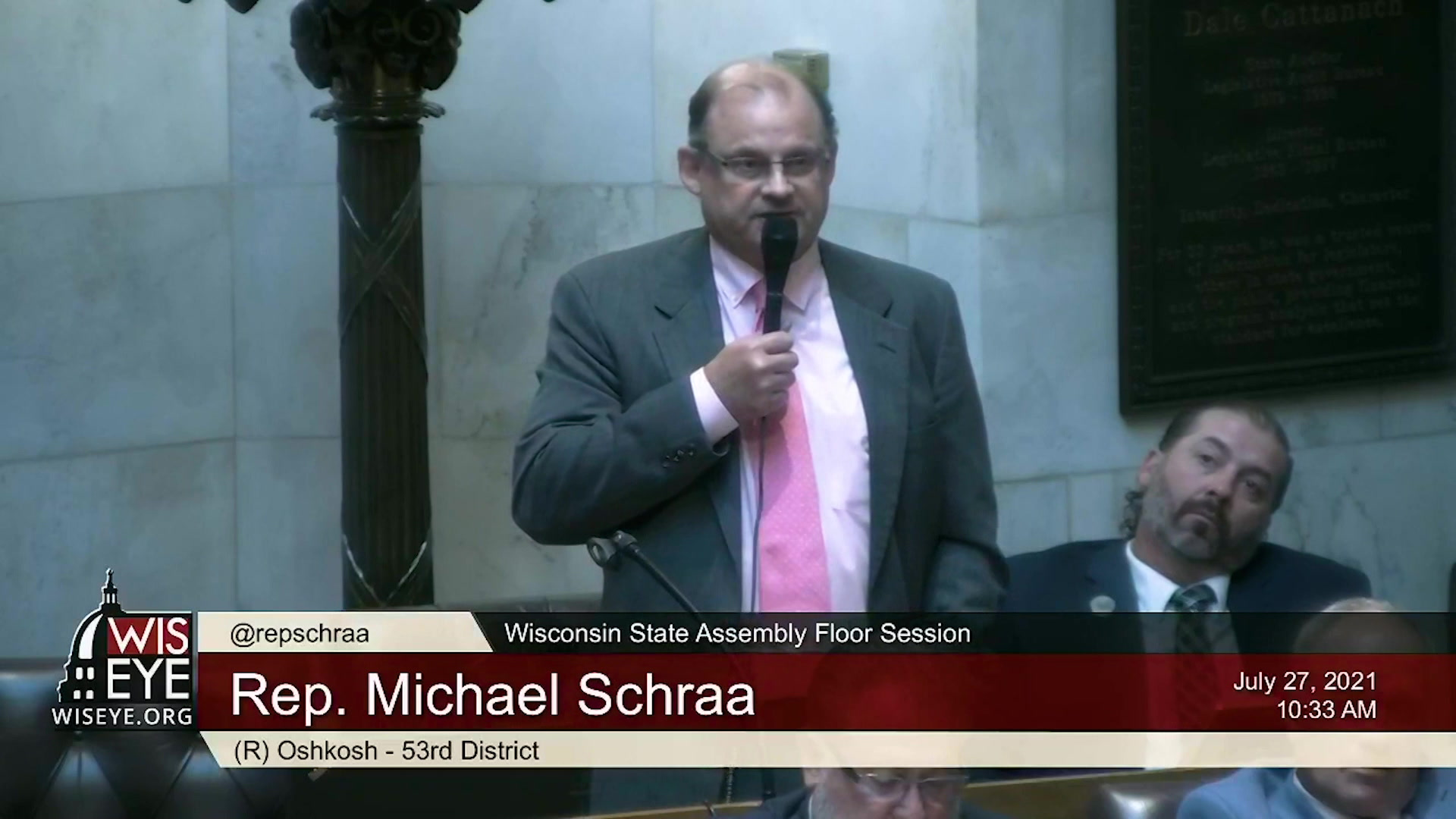 Michael Schraa holds a microphone and speaks in the Wisconsin Assembly chambers.