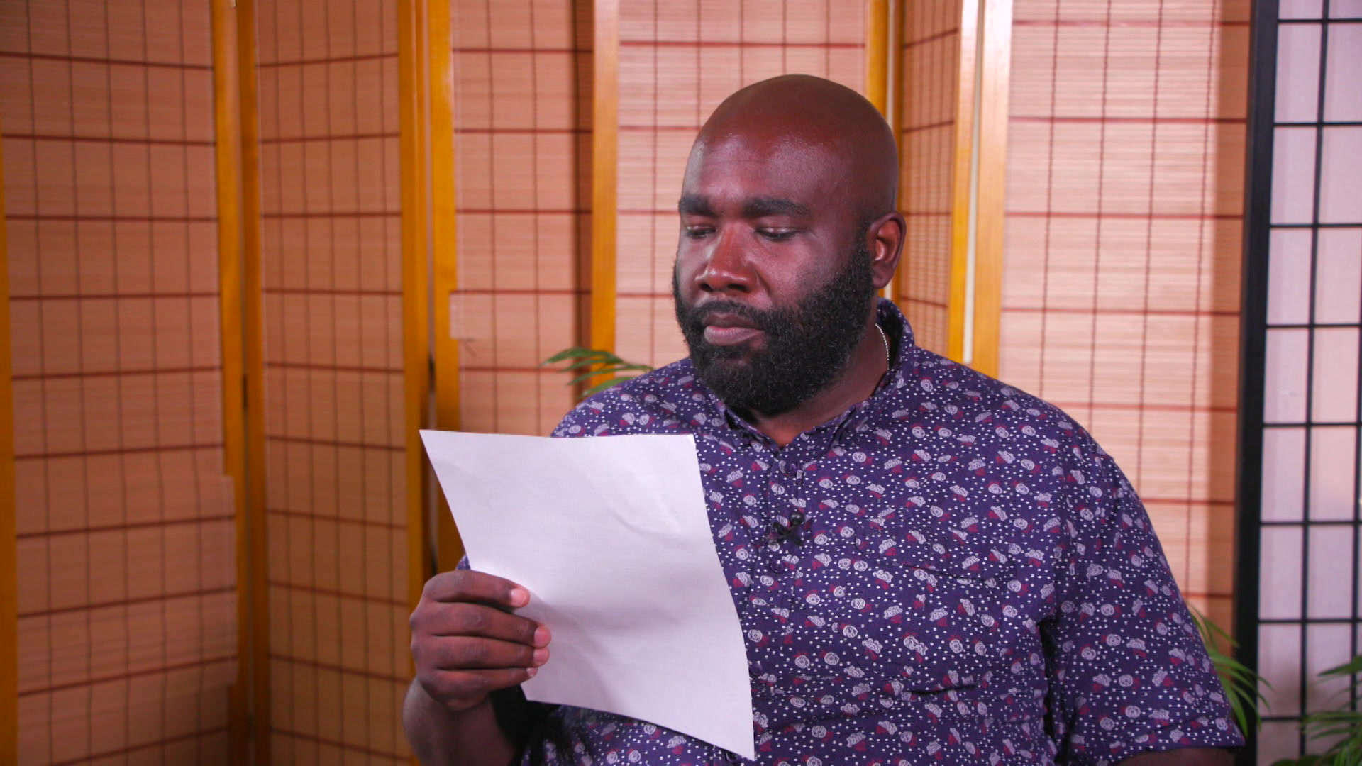 Anthony Cooper holds up and reads from a letter while seated in front of room dividers.
