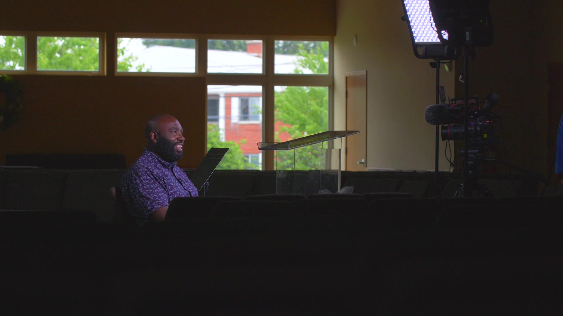 Anthony Cooper sits in a darkened room facing a video camera and lighting.