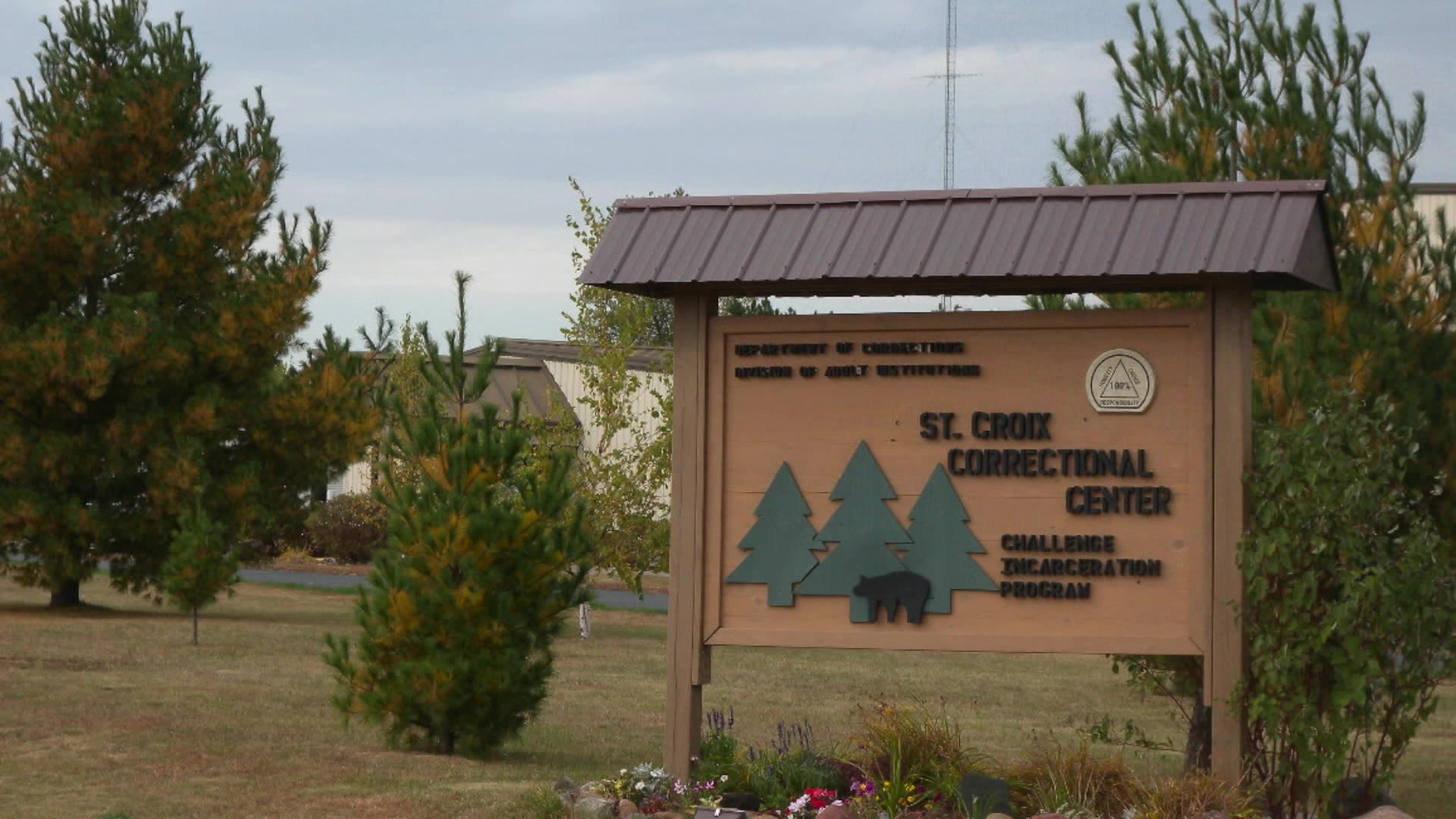 A sign for the St. Croix Correctional Center and its Challenge Incarceration Program is surrounded by pine trees.