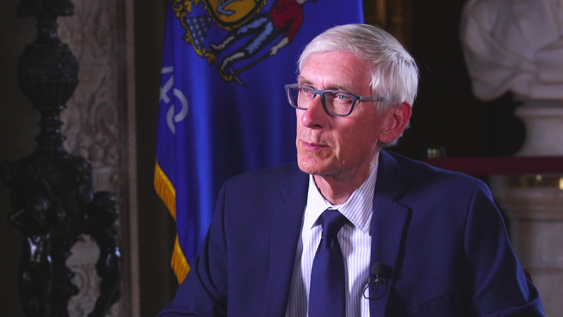Tony Evers sits in front of a Wisconsin flag.
