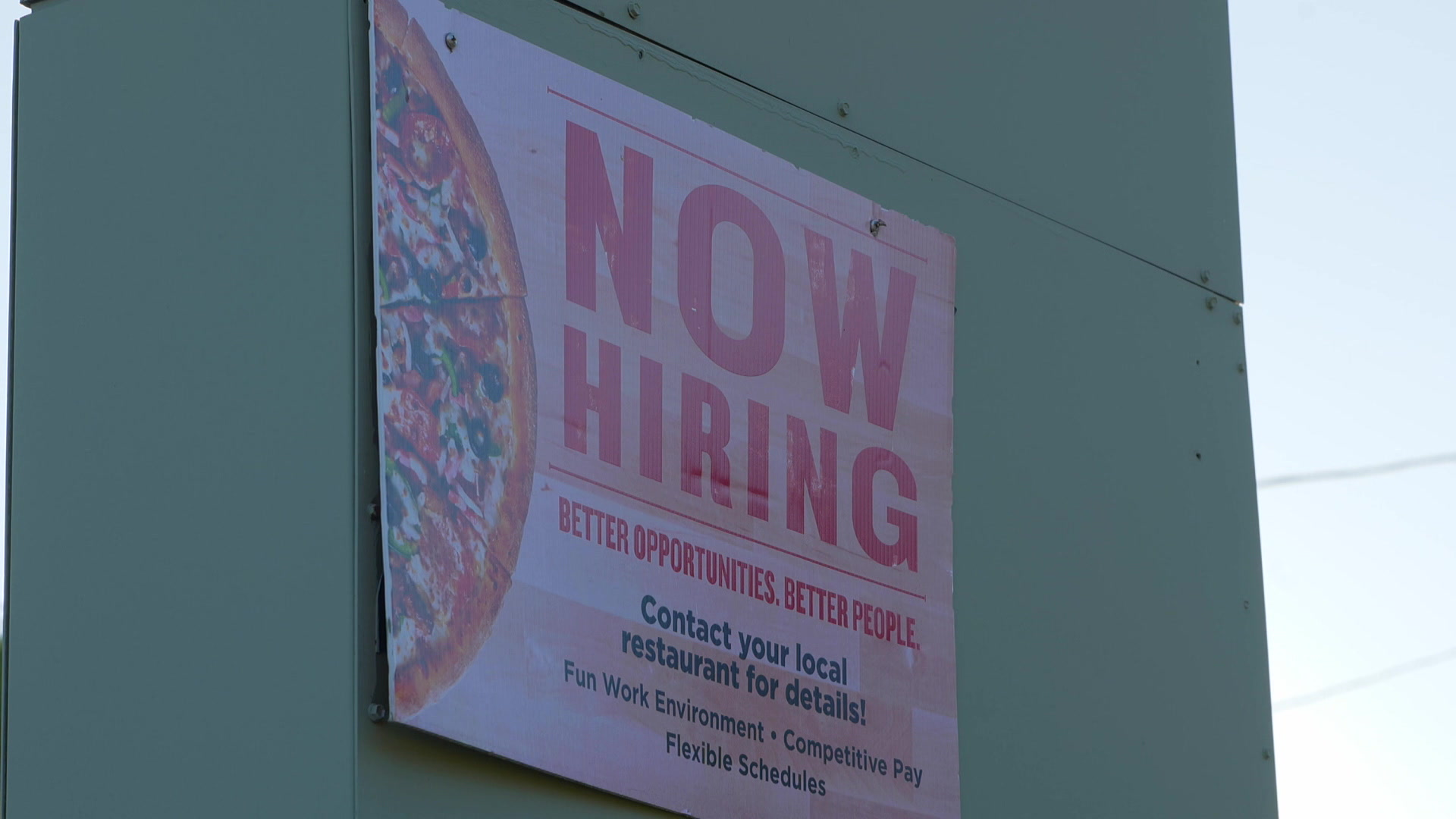 """A sign stating """"NOW HIRING"""" with a pizza graphic"""