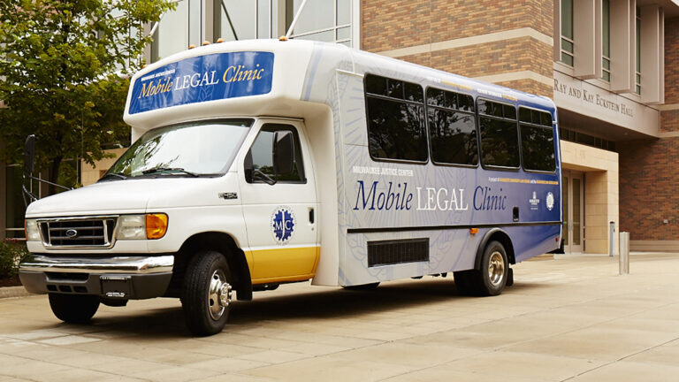 A trailer-style bus with signage stating Milwaukee Justice Center Mobile Legal Clinic is parked in front of a building.