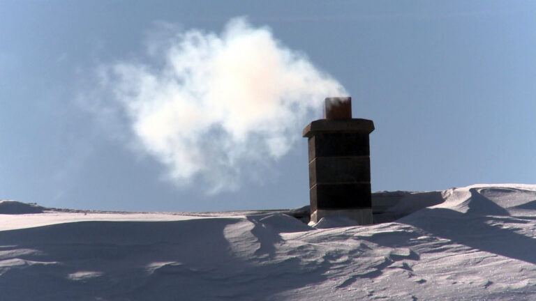 Smoke flows out of of a masonry chimney on a snow-covered roof.