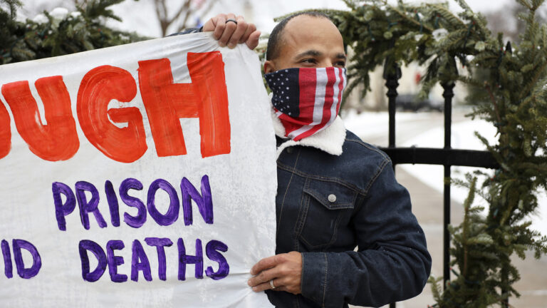 Ramiah Whiteside wears an American flag mask and holds a protest sign in front of a wrought iron fence.