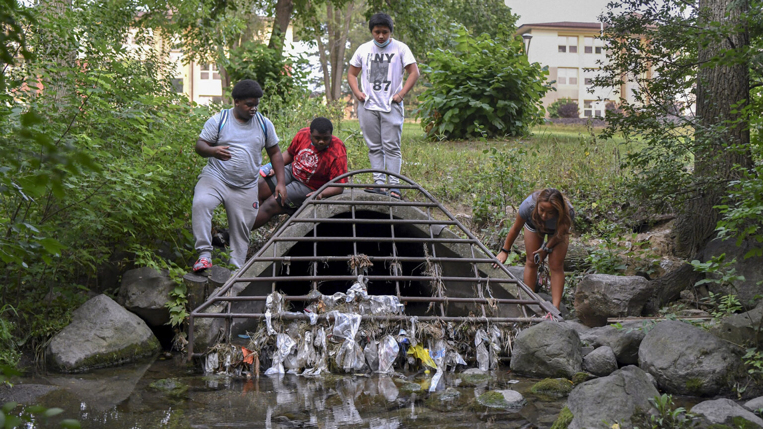 Four children stand on a concrete culvert mouth with a metal grille covered with plastic garbage on the edge of a creek.