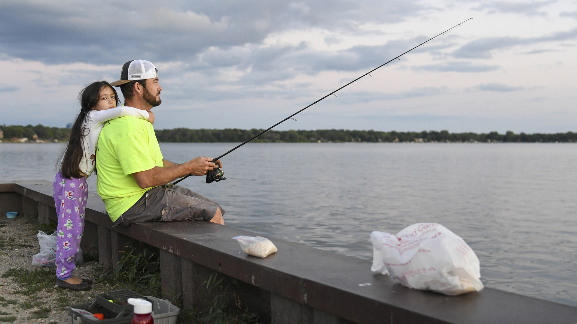 Daniel Estrada sits fishing on a dock with Isabella Estrada hugging him, with a lakeshore in the background.