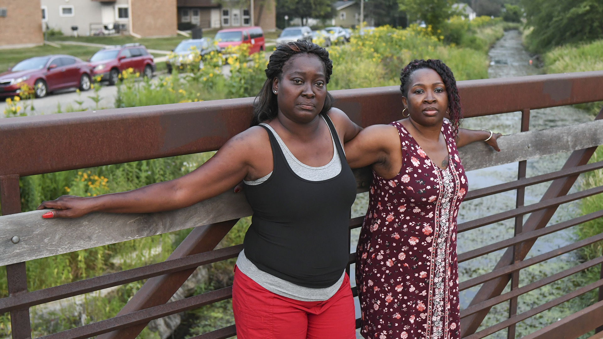 Melody Homesly and Carnetta Galvin stand on a bridge over a creek with a road and parked cars in the background.