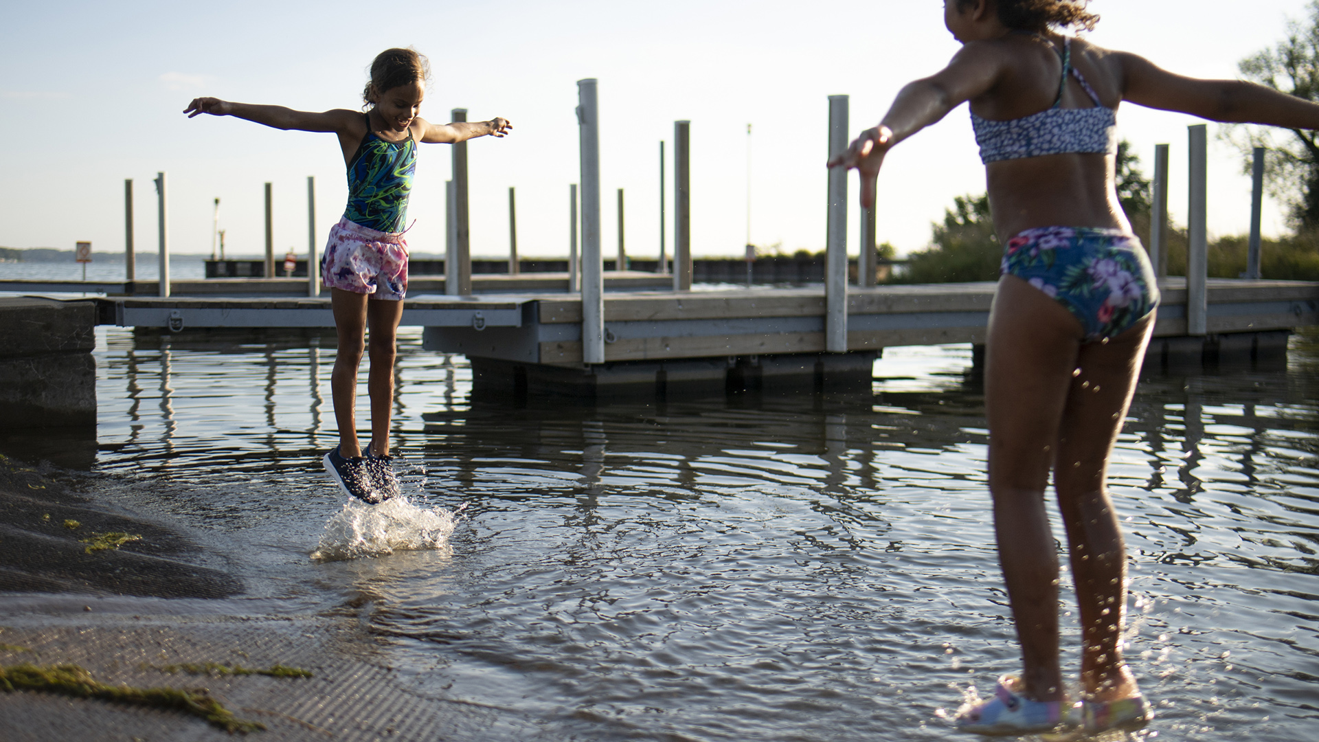 Stoni Hawkins and Terriyah Moss jump in the water at a boat launch at the mouth of a creek, with docks in the background.