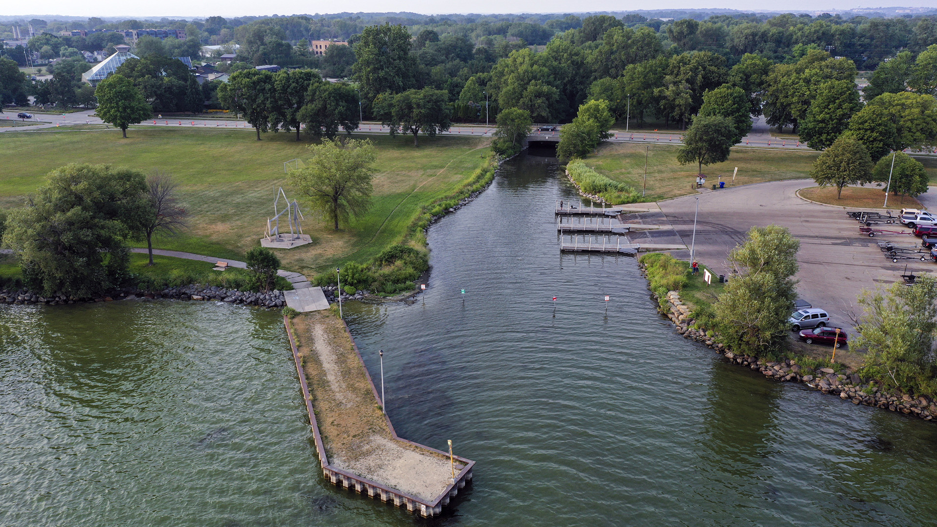 An aerial image shows a creek mouth on a lake in the middle of a park, with docks, boat launches and and a parking lot.
