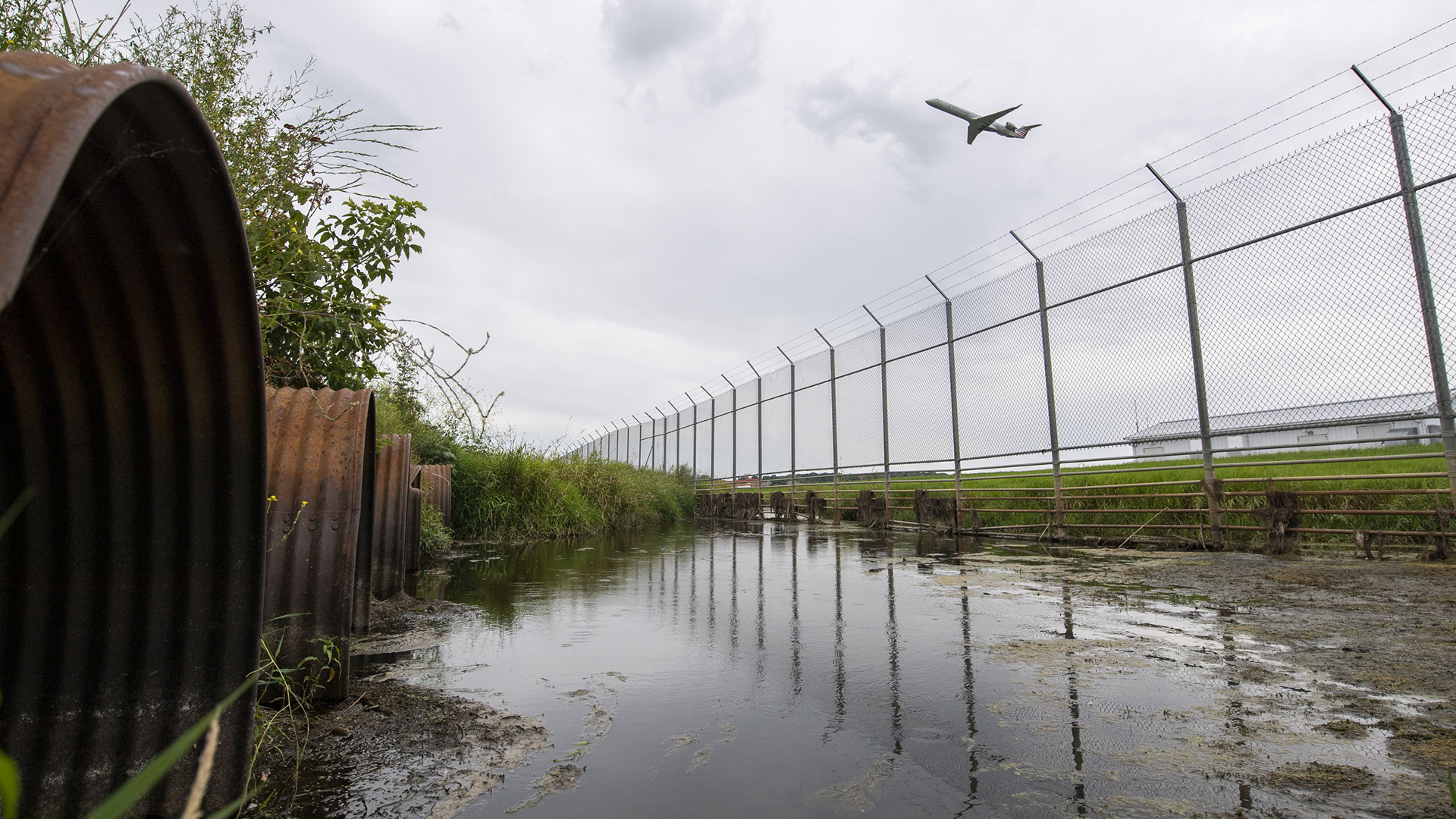 An airplane ascends over a chain-linked fence topped with barbed wire that faces a wetland area with rusty culvert mouths.