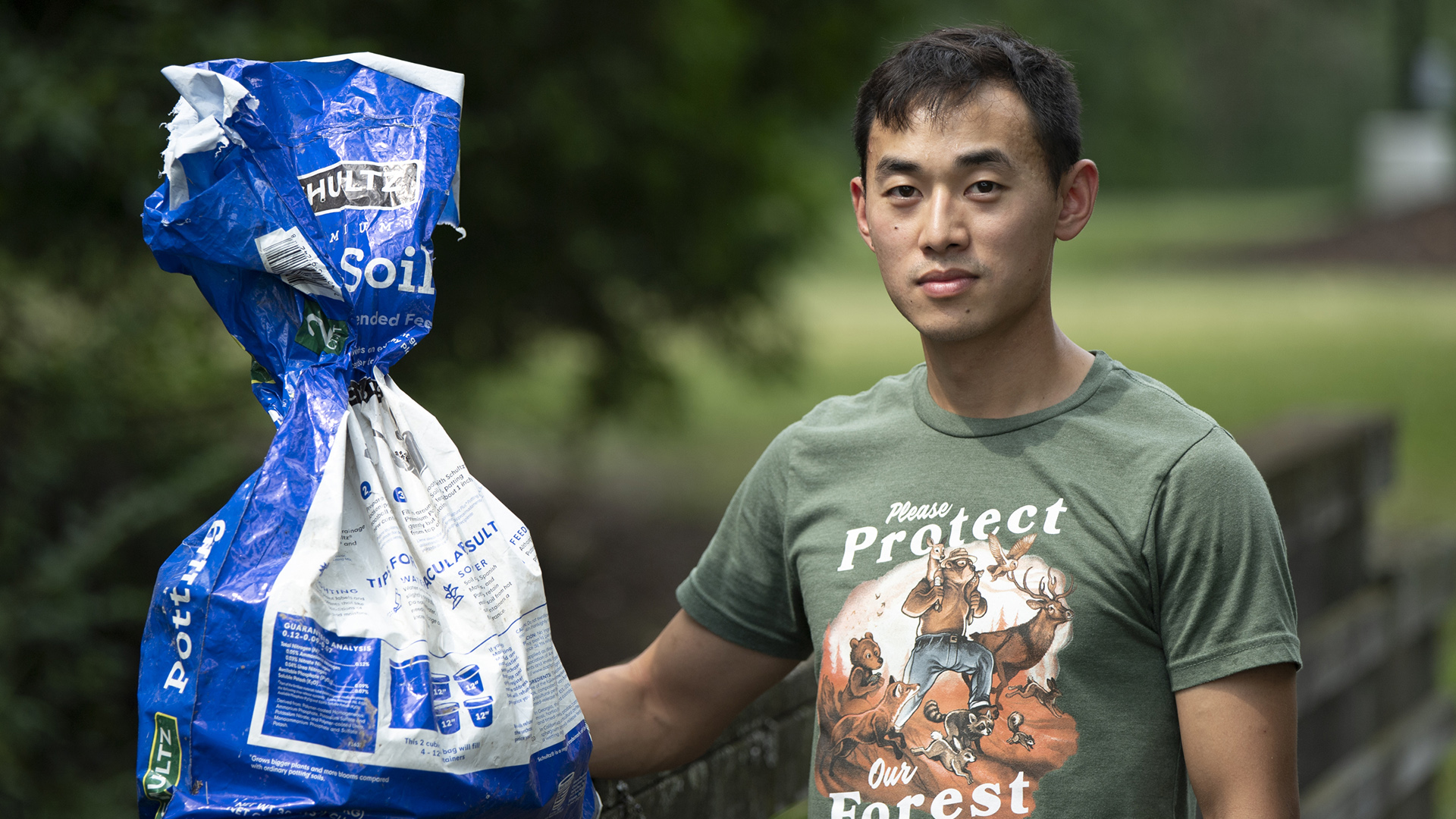 Touyeng Xiong holds a garden soil bag filled with garbage.